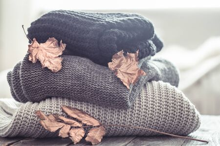 a stack of knitted cozy sweaters of different colors on a wooden background. the concept of warmth and comfort
