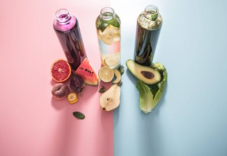 Glass bottles with natural detox drinks and a variety of fruits and vegetables on a colored background . Healthy food and drink concept. The view from the top. Stock Photo