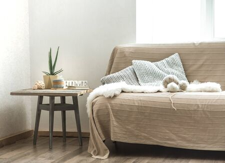 Home sofa with objects of cozy decor in the living room on a chair . The concept of decor and home atmosphere . Stock Photo