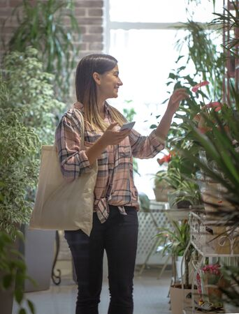 A girl in a plaid shirt with eco bag comes into the store and greets the sellers.