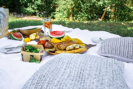 A white blanket on the green grass. The concept of a picnic. Background, top view. Place for text . A variety of summer products in nature .