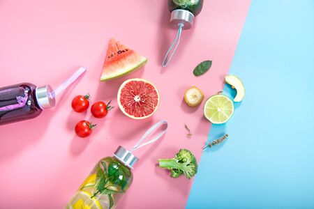Glass bottles with natural detox drinks and a variety of fruits and vegetables on a colored background . Healthy food and drink concept. The view from the top. Banque d'images - 130159467