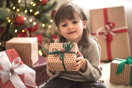 Pretty little girl is holding a gift box and smiling while sitting on her bed in her room at home. Happy Holidays. Gifts and presents Stock fotó