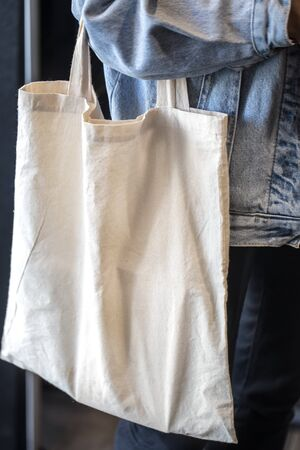 Girl dressed in denim jacket holding eco-bag. Close up of woman holding eco or reusable shopping bag. No plastic bag and ecology concept. Copy space.