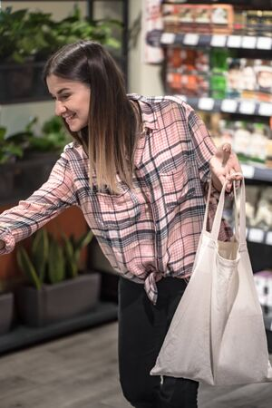 The girl dressed in a plaid shirt holding an eco-bag. Close up of woman holding eco or reusable shopping bag. No plastic bag and ecology concept. Copy space.