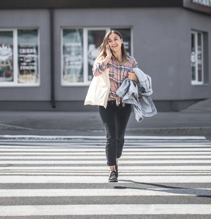 Young girl crossing the road at a pedestrian crossing with eco bag and phone. Reklamní fotografie