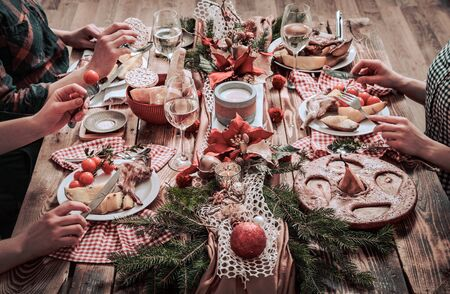 Flat-lay of friends hands eating and drinking together. Top view of people having party, gathering, celebrating together at wooden rustic table set with different wine snacks and fingerfoods Stock Photo