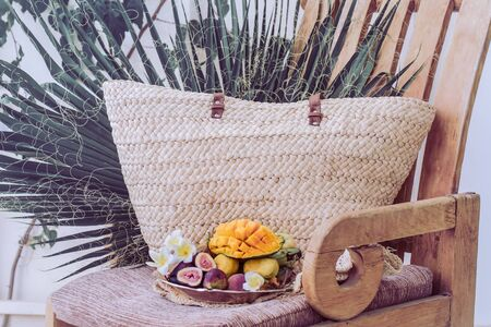 Plate with assorted fruits, sliced mango. Stands on a wooden chair next to a large wicker basket and palm leaves