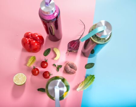 Glass bottles with natural detox drinks and a variety of fruits and vegetables on a colored background . Healthy food and drink concept. The view from the top. Zdjęcie Seryjne