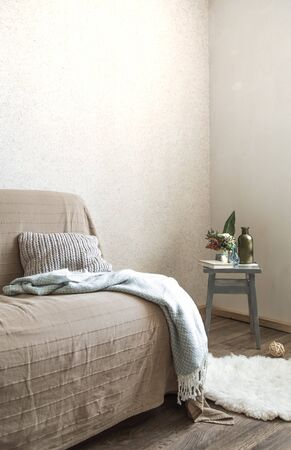 Home sofa with objects of cozy decor in the living room on a chair . The concept of decor and home atmosphere . 写真素材