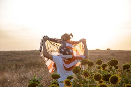 Happy family, dad and daughter holding the American flag at sunset. Dressed in white. The concept of family values and friendship . Patriotic feeling. 写真素材