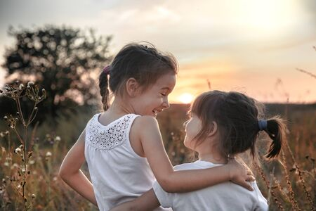 Two little sisters hugging in a field at sunset . Dressed in white. The concept of family values and friendship . 写真素材