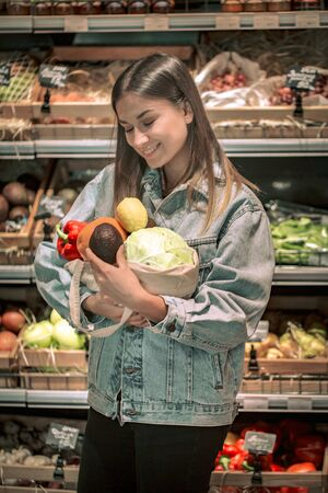 Young girl holding fruits and vegetables in an eco bag on the background of the store. 写真素材