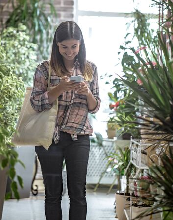 A girl with eco bag in a plaid shirt comes into the store and looks at the phone.