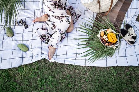 Summer picnic, a girl with a plate of fruit on a white Mat . The concept of summer parties, food and recreation . The view from the top . Reklamní fotografie