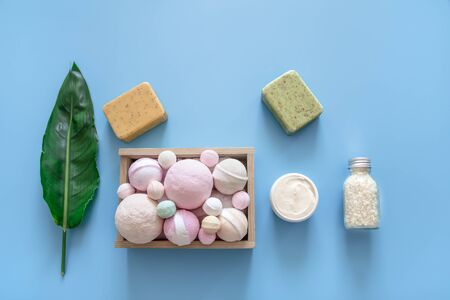 Spa composition with body care items and tropical leaf on a colored background . Spa and body care concept . Flatlay.