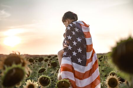 a little girl holds an American flag on her shoulders, at sunset in a beautiful field. Patriotic feeling.