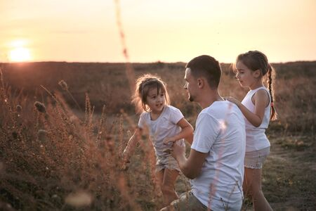 Dad with two daughters playing in the field at sunset . Dressed in white. The concept of family values and friendship .