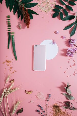 Back of phone with white circle shape in flowers on pink background. Flat lay. Top view.