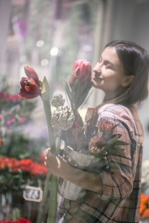 A young girl in a plaid shirt chooses and creates a composition of flowers in a flower shop. Stockfoto