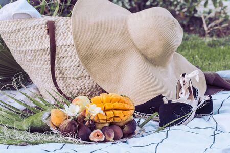 Summer picnic with a plate of tropical fruits . With a stylish wicker bag and a large beach hat . Summer time concept of healthy eating.