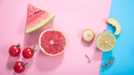 Different fruits and vegetables on a colored background. Flat-lay. The view from the top. Zdjęcie Seryjne