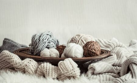 Still life with a cozy variety of yarn for knitting in the interior of the living room. The concept of hobby and comfort .