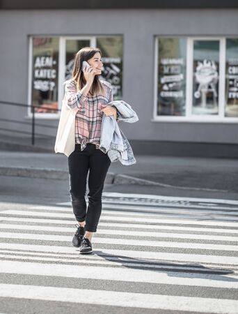 Young girl crossing the road at a pedestrian crossing with eco bag and phone. Stock Photo