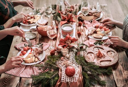 Flat-lay of friends hands eating and drinking together. Top view of people having party, gathering, celebrating together at wooden rustic table set with different wine snacks and fingerfoods Stock Photo - 130158755