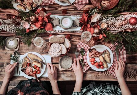 Flat-lay of friends hands eating and drinking together. Top view of people having party, gathering, celebrating together at wooden rustic table set with different wine snacks and fingerfoods Stock Photo - 130158759
