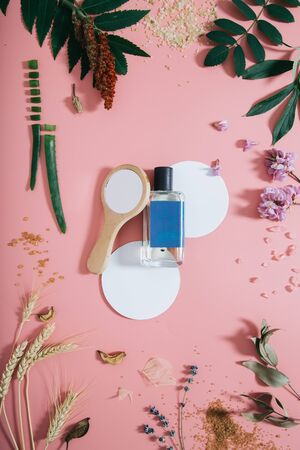 Perfume bottle in flowers on pink background with white circle shape and mirror. Spring background with aroma parfume. Beauty cosmetic, fresh aromatic. Flat lay