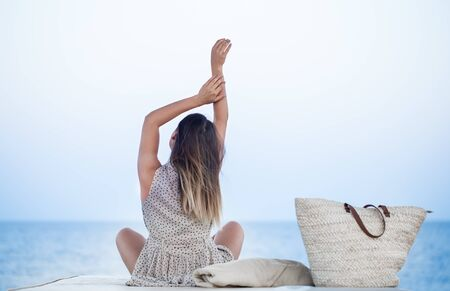 A young woman in a dress sits by the sea and relaxes. Sea view. The concept of relaxation . Stock fotó