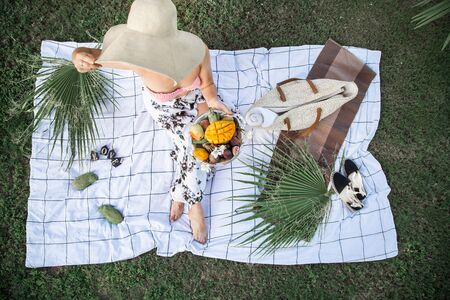 A summer picnic, a girl in a big beautiful beach hat , with a plate of fruit on a white Mat . The concept of summer parties, food and recreation .