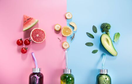 Glass bottles with natural detox drinks and a variety of fruits and vegetables on a colored background . Healthy food and drink concept. The view from the top. Фото со стока
