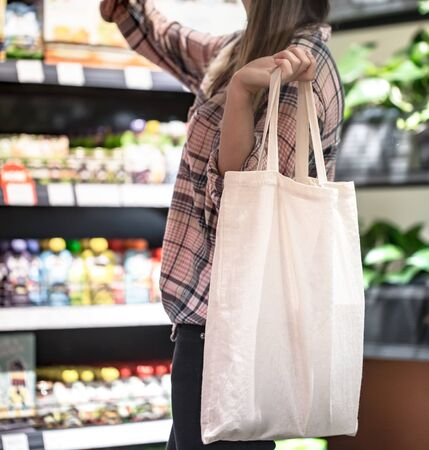 The girl dressed in a plaid shirt holding an eco-bag. Close up of woman holding eco or reusable shopping bag. No plastic bag and ecology concept. Copy space. Foto de archivo - 130158607