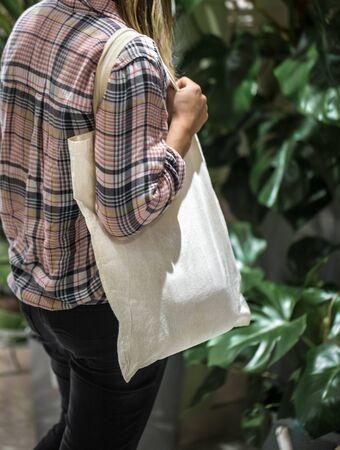 The girl dressed in a plaid shirt holding an eco-bag. Close up of woman holding eco or reusable shopping bag. No plastic bag and ecology concept. Copy space. Foto de archivo - 130158631