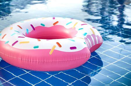 Inflatable accessories for swimming in the pool . In the form of inflatable large pink doughnut. The concept of summer vacation.
