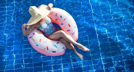 The woman in the hat relaxes on an inflatable circle in the form of a donut in the blue pool. The view from the top . The concept of summer pastime . 스톡 콘텐츠