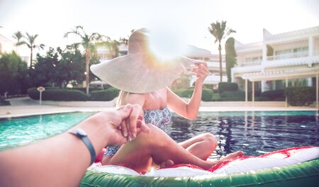 Summer holiday by the pool . A woman relaxes on an inflatable circle in the form of a donut in the pool. Holding a friends hand. Summer entertainment and pastime .