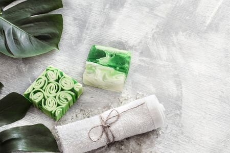Flat-lay natural beautiful cosmetics handmade soap with tropical leaves on a light background, top view