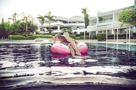 Summer holiday by the pool . A woman in a hat relaxes on an inflatable donut in a blue pool . Summer fun and hanging out .