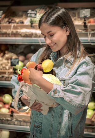 Young girl holding fruits and vegetables in an eco bag on the background of the store. Stock Photo
