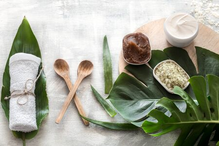 Flat-lay natural cosmetics and accessories with tropical leaves to cleanse the skin. Basic hygiene and body care items on white background, copy space.