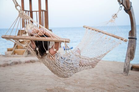 A young woman sits in a hammock by the sea and relaxes. Sea view. The concept of relaxation .