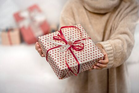 A woman in a warm sweater, holding a beautiful Christmas gifts. Holiday concept. Close up.