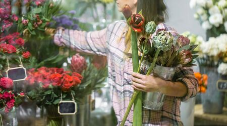 A young girl in a plaid shirt chooses and creates a composition of flowers in a flower shop. Banco de Imagens