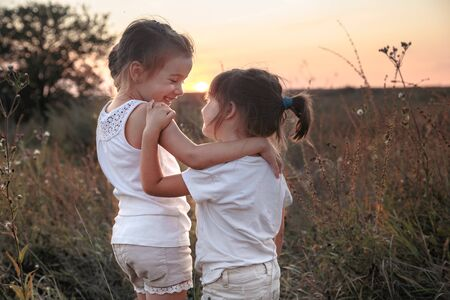 Two little sisters hugging in a field at sunset . Dressed in white. The concept of family values and friendship .