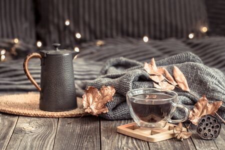 Cozy autumn still life with a Cup of tea in a homely atmosphere on a wooden table. Reklamní fotografie