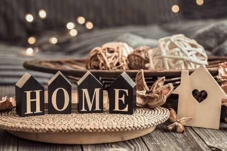 Still life with objects of festive home decor and wooden letters with the inscription home, near a small wooden house. Stock fotó