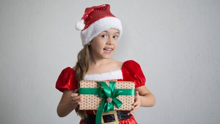 portrait of a little girl dressed in Christmas costume with gifts on a light background. Festive concert.